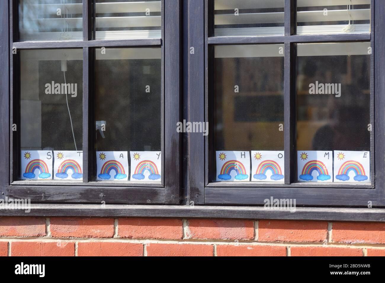 Rainbow fotos para la esperanza y positividad con el mensaje 'Stay Home' exhibida en la casa en el Reino Unido durante el cierre del Coronavirus Covid-19 Foto de stock