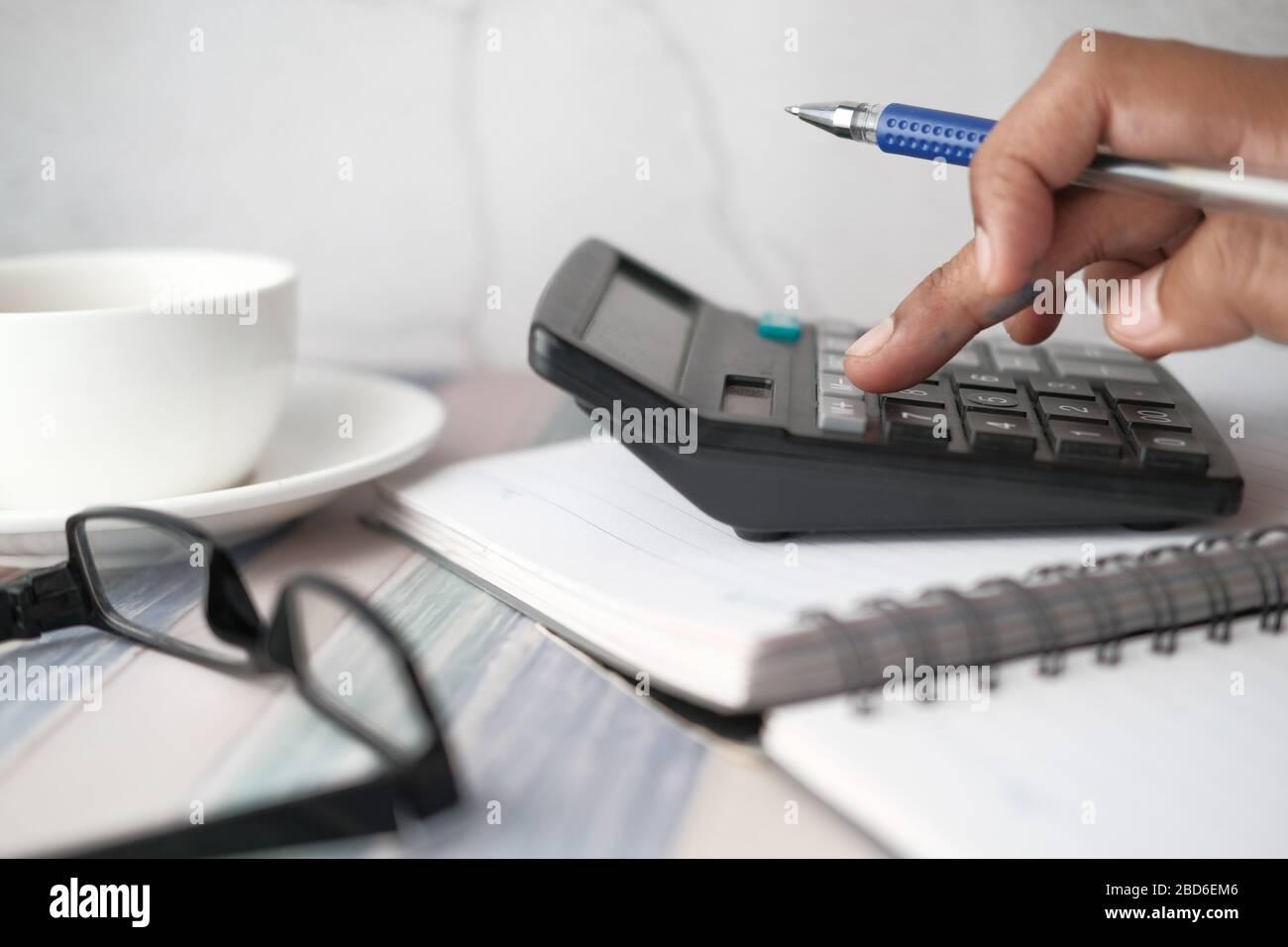 Primer plano de la mano de hombre utilizando la calculadora y el gráfico financiero sobre la mesa Foto de stock