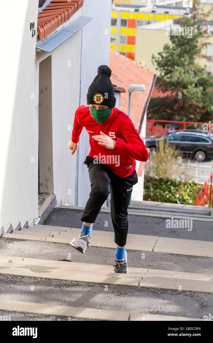 niño corriendo arriba con mascarilla quirúrgica casera Foto de stock