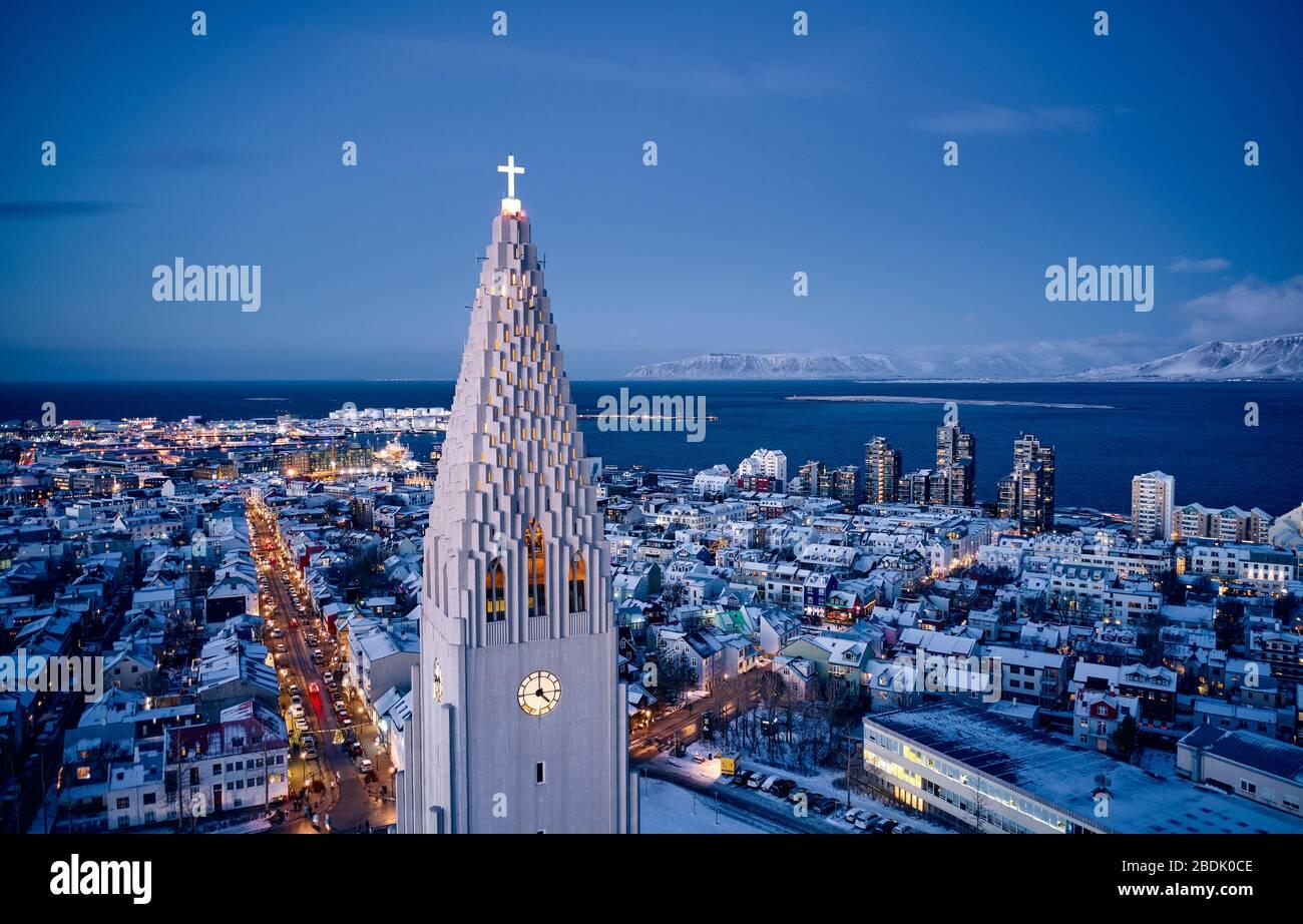 Vista aérea de la moderna torre blanca de la alta iglesia Hallgrimskirkja con una cruz brillante en el centro moderno de la ciudad al atardecer en Islandia Foto de stock