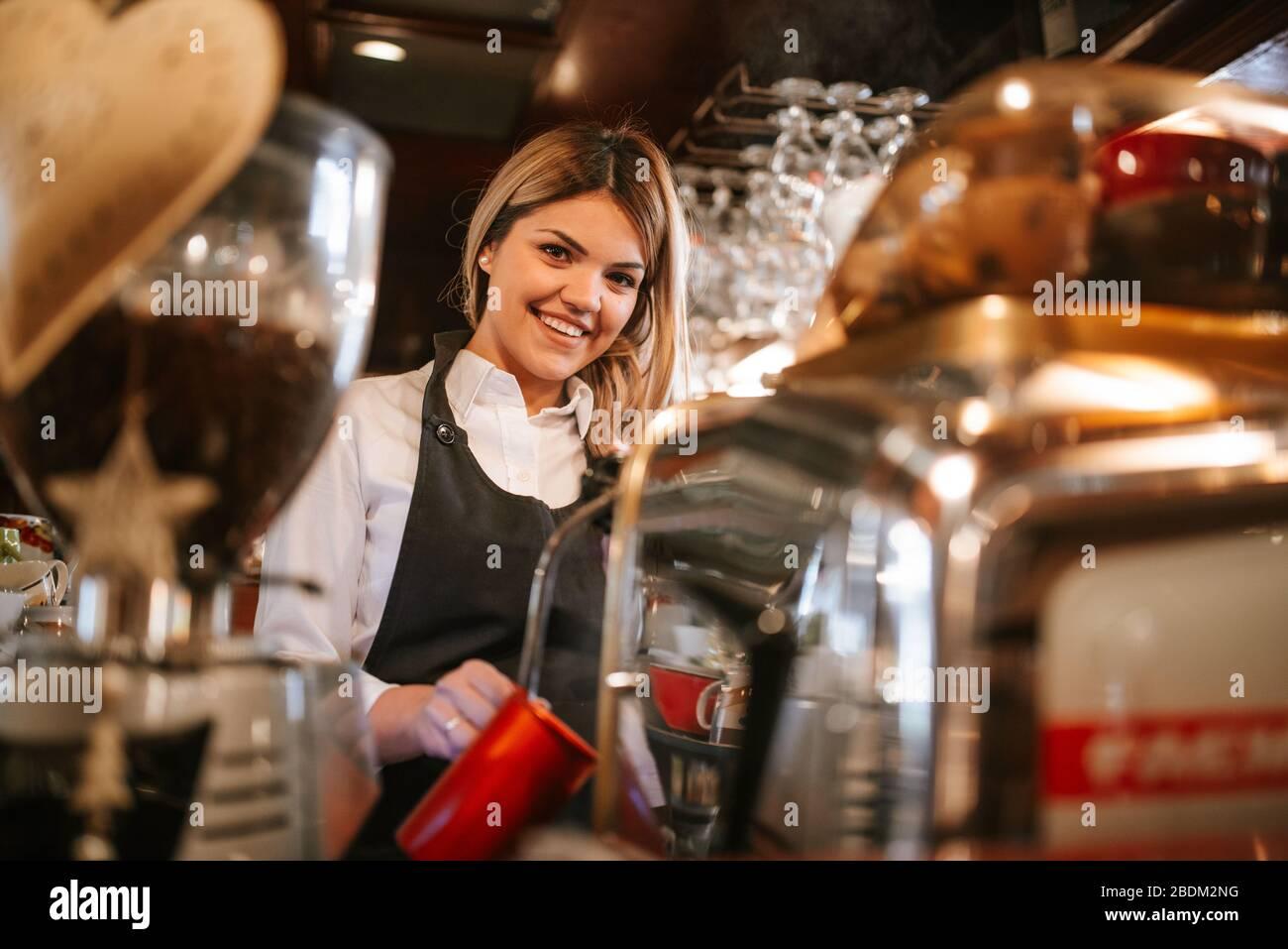 Una joven y atractiva camarera rubia caucásica hace café en un café Foto de stock