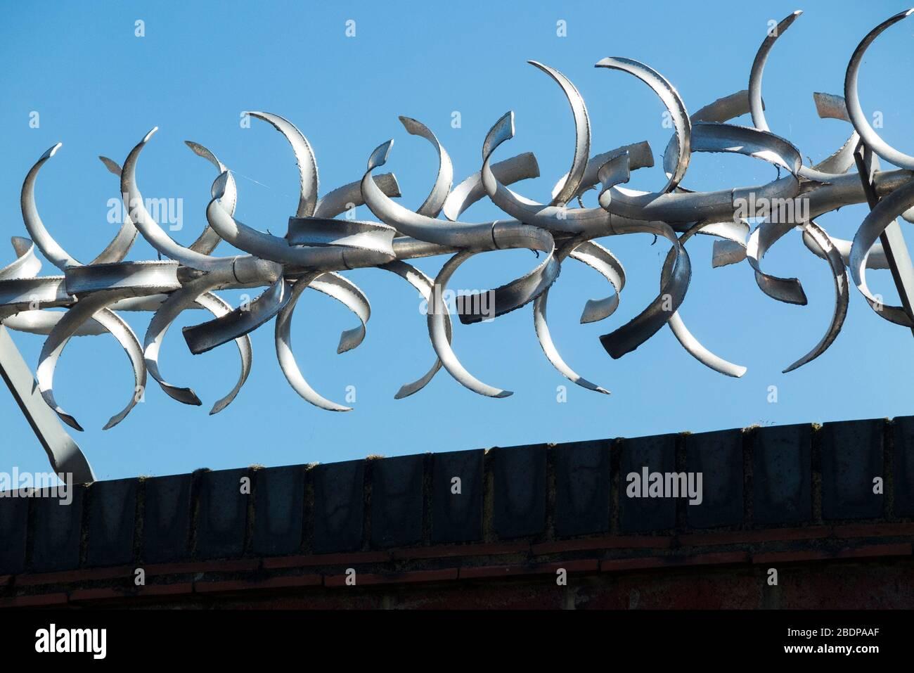 Pared de ladrillo alta y alta con moderna barrera de seguridad giratoria con púas curvas / bordes de álabes de afeitar en la parte superior, para fines de seguridad. (116) Foto de stock