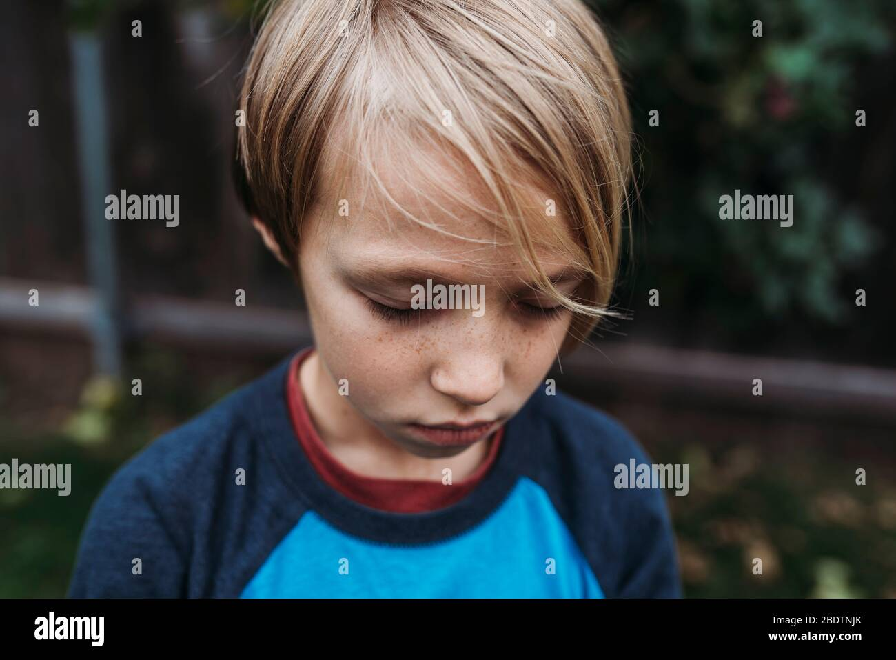 Primer plano de niño con los ojos cerrados y pecas Foto de stock