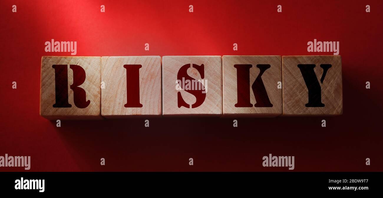 Palabra arriesgada sobre bloques de madera sobre fondo rojo. Activos de riesgo, riesgo financiero en concepto de inversión empresarial. Concepto de prevención del virus de Dangeruos Foto de stock
