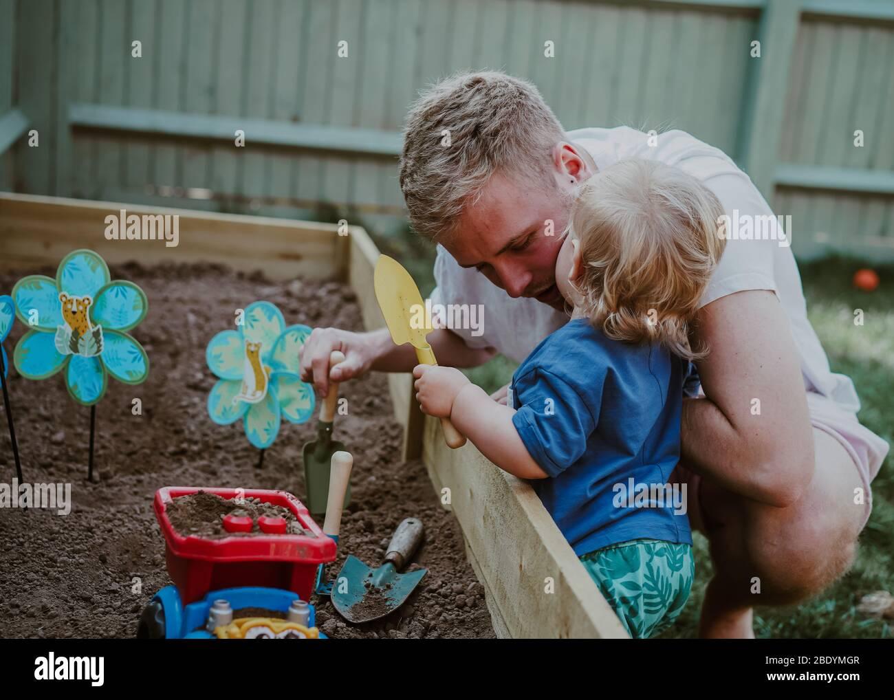 Niño pequeño niño pequeño jugando en el jardín con papá Foto de stock
