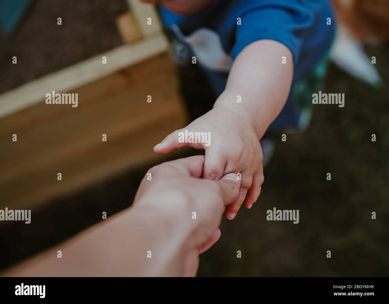 POV (punto de vista) pequeño niño sosteniendo la mano de mamá Foto de stock