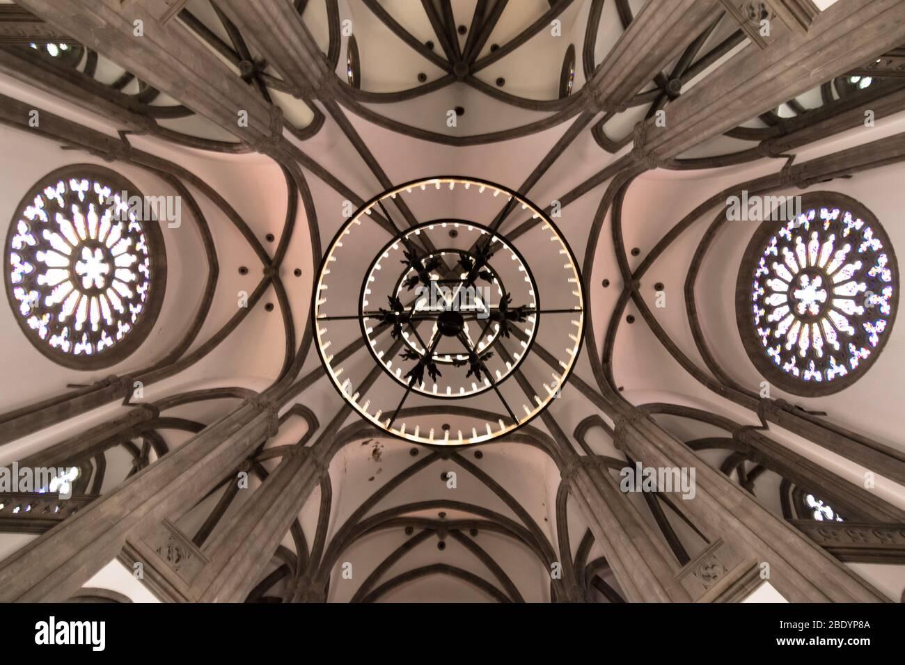 Techo de una iglesia con arcadas, ventanas de rosas y una lámpara de vela colgante. Concepto de religión Foto de stock