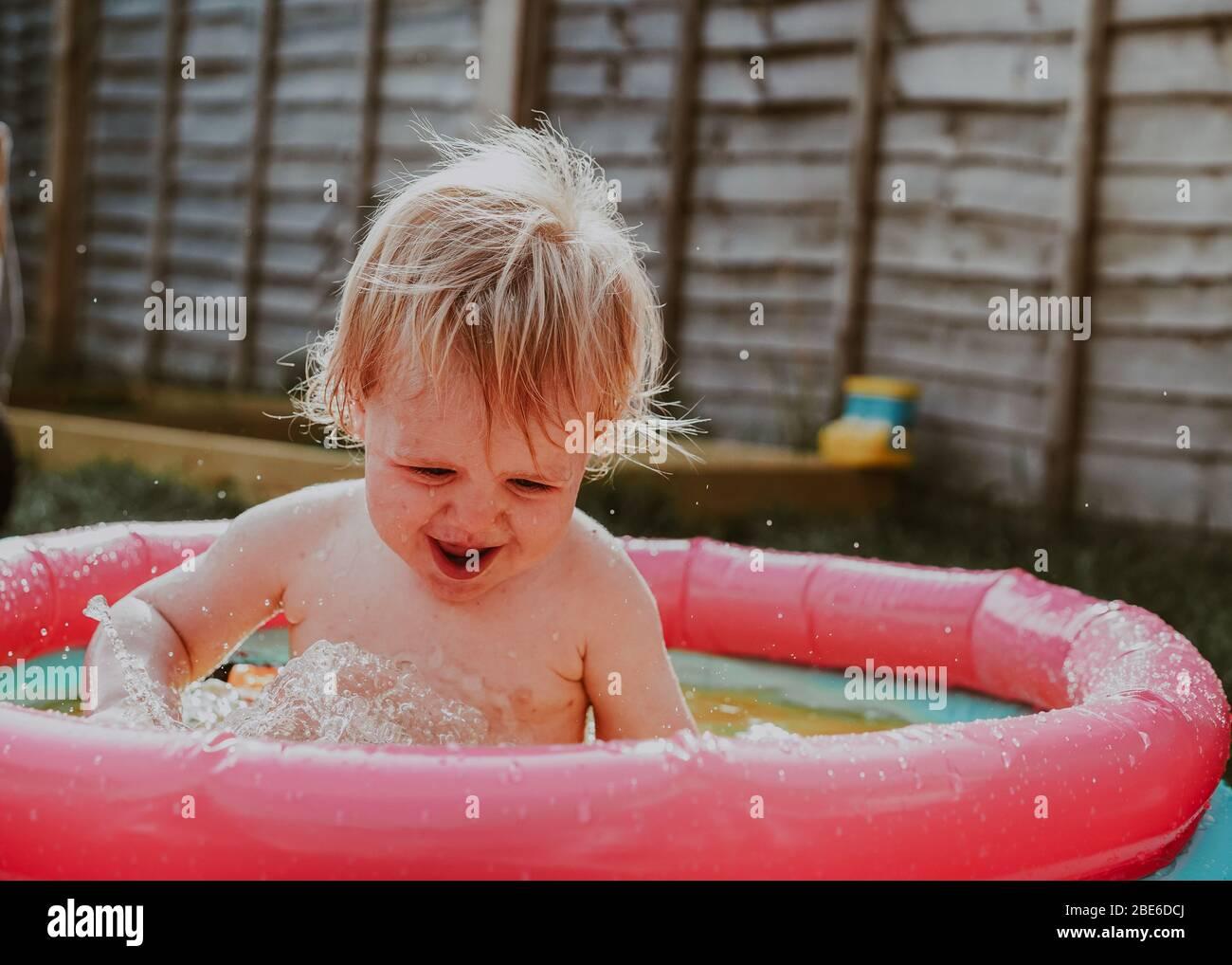 Pequeño robot niño jugando en la piscina infantil en el jardín en verano, Reino Unido Foto de stock