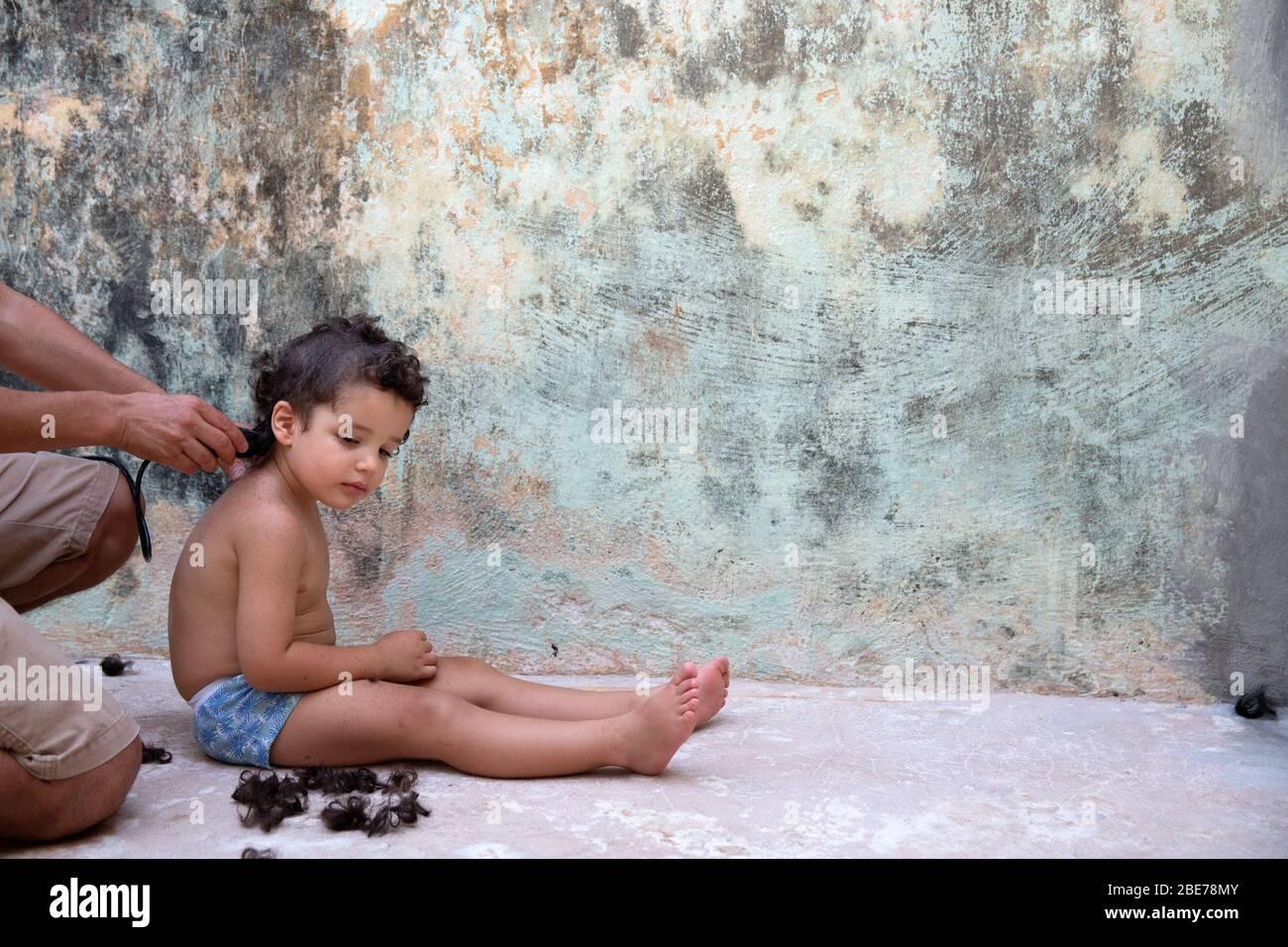 """Thiago tiene la cabeza afeitada por su padre en su vigésimo primer día de auto-aislamiento debido a la pandemia de Covid-19 en un hogar temporal en Mérida, Yucatán, México el 4 de abril de 2020. El fotógrafo Benedicte Desrus dijo: """"Toda la familia decidió afeitarse la cabeza, ya que entendemos que esta cuarentena podría durar varios meses y el tiempo es ahora de 42 grados Celsius aquí. Además, es una manera de recordar lo que vivimos en el futuro."""" Thiago, de 3 años, es hijo del fotógrafo. Fue documentado como parte de un proyecto titulado """"cuando crecí"""" sobre un niño que crecía en cuarentena, lejos de otros Foto de stock"""