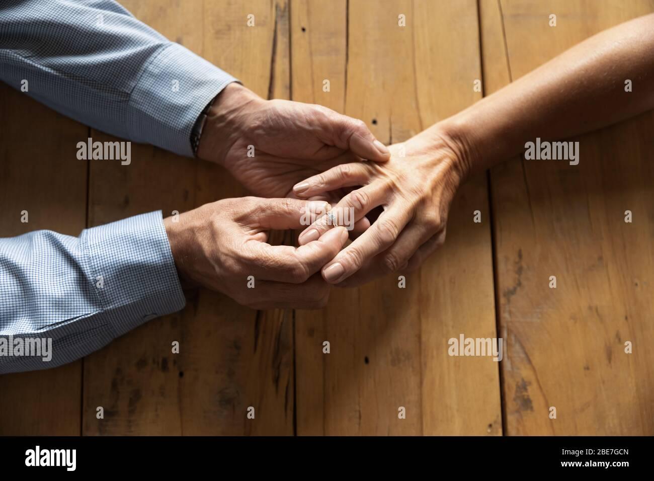 Hombre mayor poniendo anillo de compromiso en la mujer dedo cerca de arriba Foto de stock