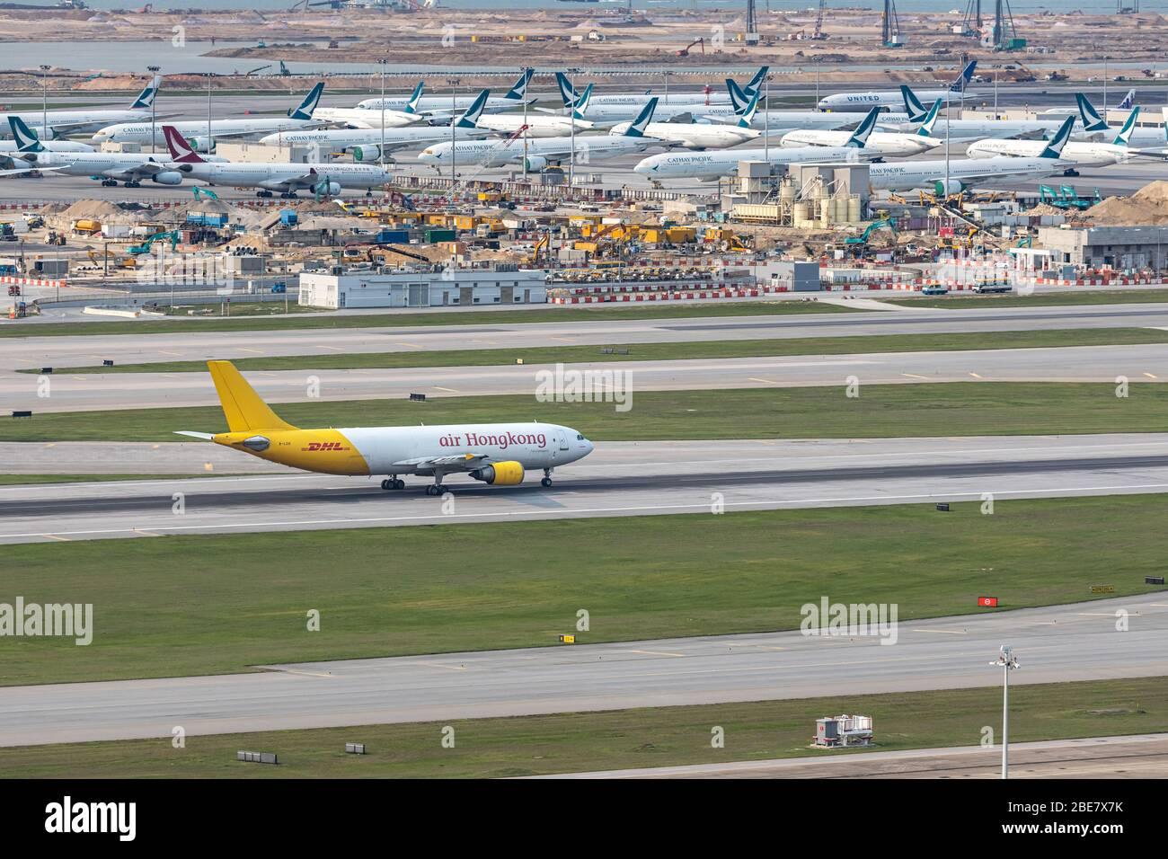 Lantau, Hong Kong - 10 de abril de 2020 : el avión de carga de Air Hong Kong está en funcionamiento para despegue en la pista, todo el espacio de estacionamiento está completamente ocupado debido a Foto de stock