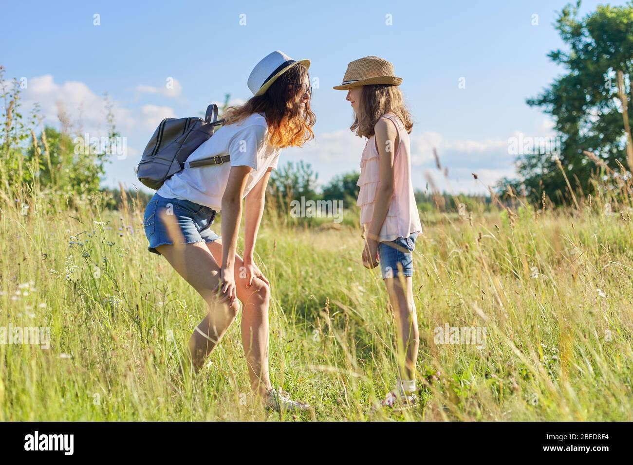 Niños felices dos niñas hermanas adolescentes y jóvenes riendo y divertirse en la pradera, el cielo azul, la naturaleza de verano. Estilo de vida activo y saludable, amigable f Foto de stock