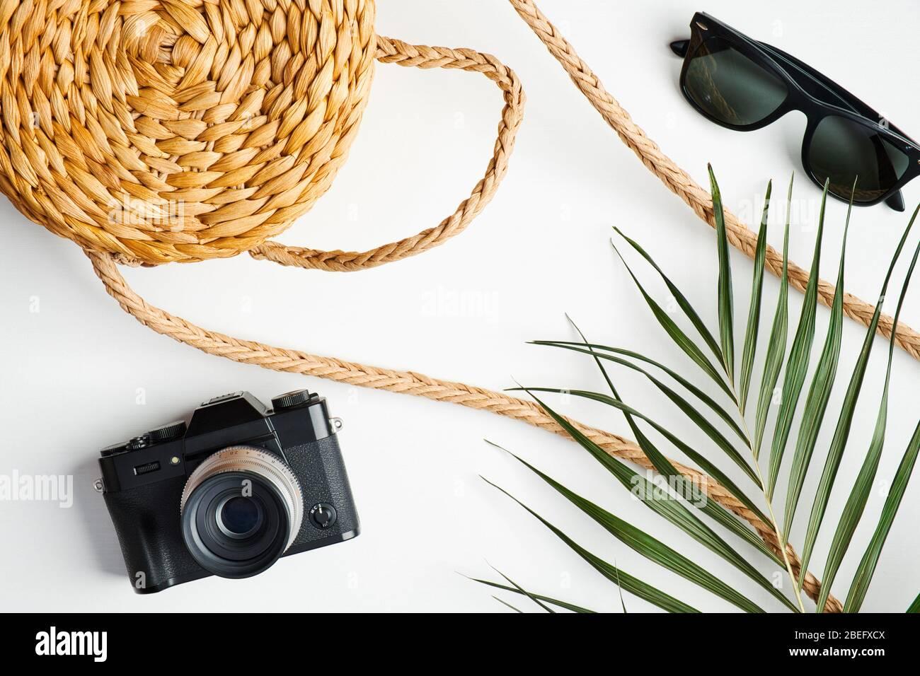 Ropa femenina de moda de verano con bolso de ratán, cámara de época, gafas de sol, hoja de palma tropical sobre mesa blanca. Concepto de viaje, vacaciones, vacaciones. FL Foto de stock