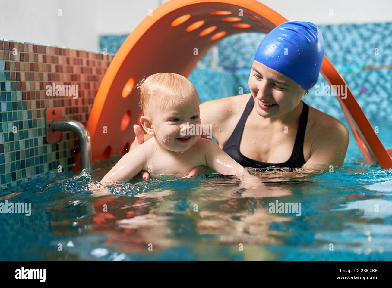 Muy interesante entrenamiento activo en piscina. Un niño lindo está aprendiendo a flotar con su madre de apoyo. Concepto de familia sana Foto de stock