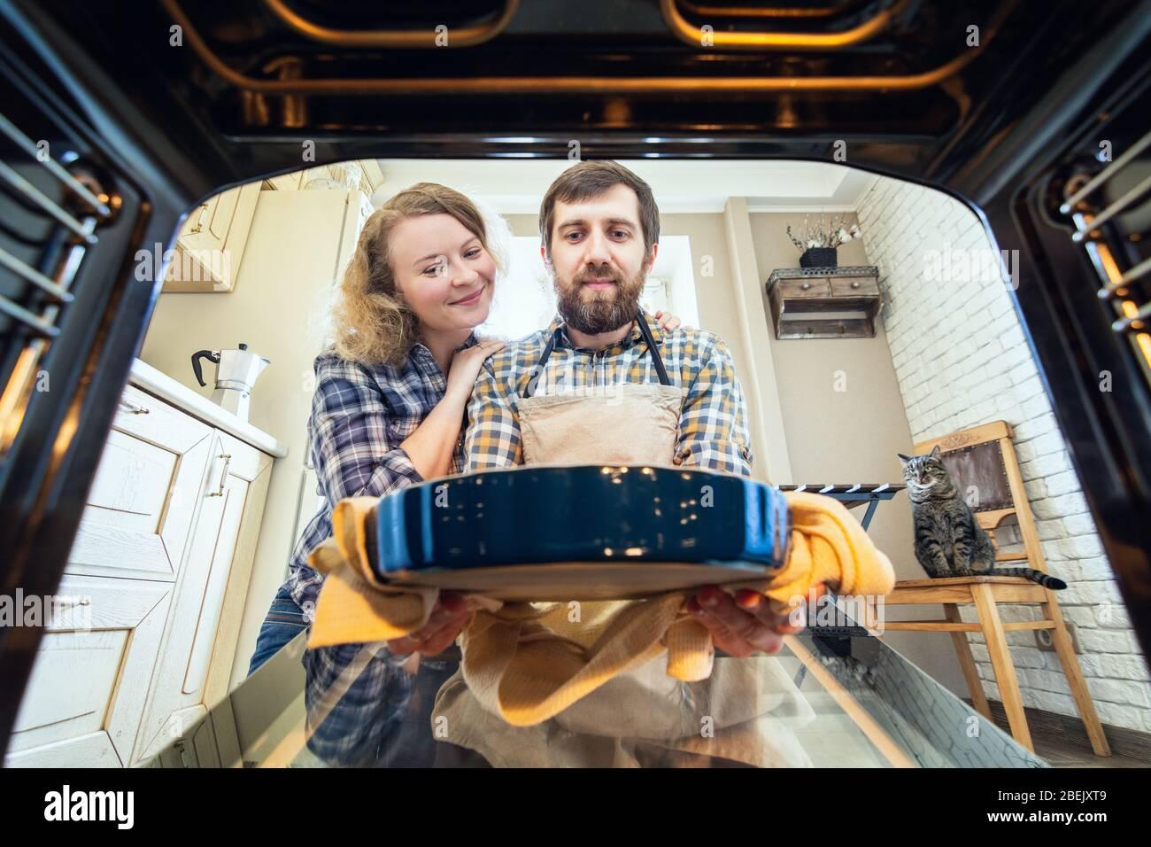 Una pareja sonriente de Europa del este cocinando en casa. Hombre sacando una tarta del horno con cocina interior y un gato en el fondo, vista desde dentro Foto de stock