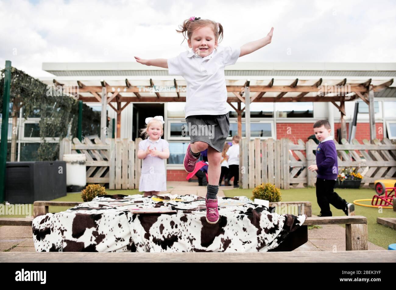 Niños en el área de juegos al aire libre en una escuela de párvulos en Darlington, County Durham, Reino Unido. 18/4/2018. Fotografía: Stuart Boulton. Foto de stock