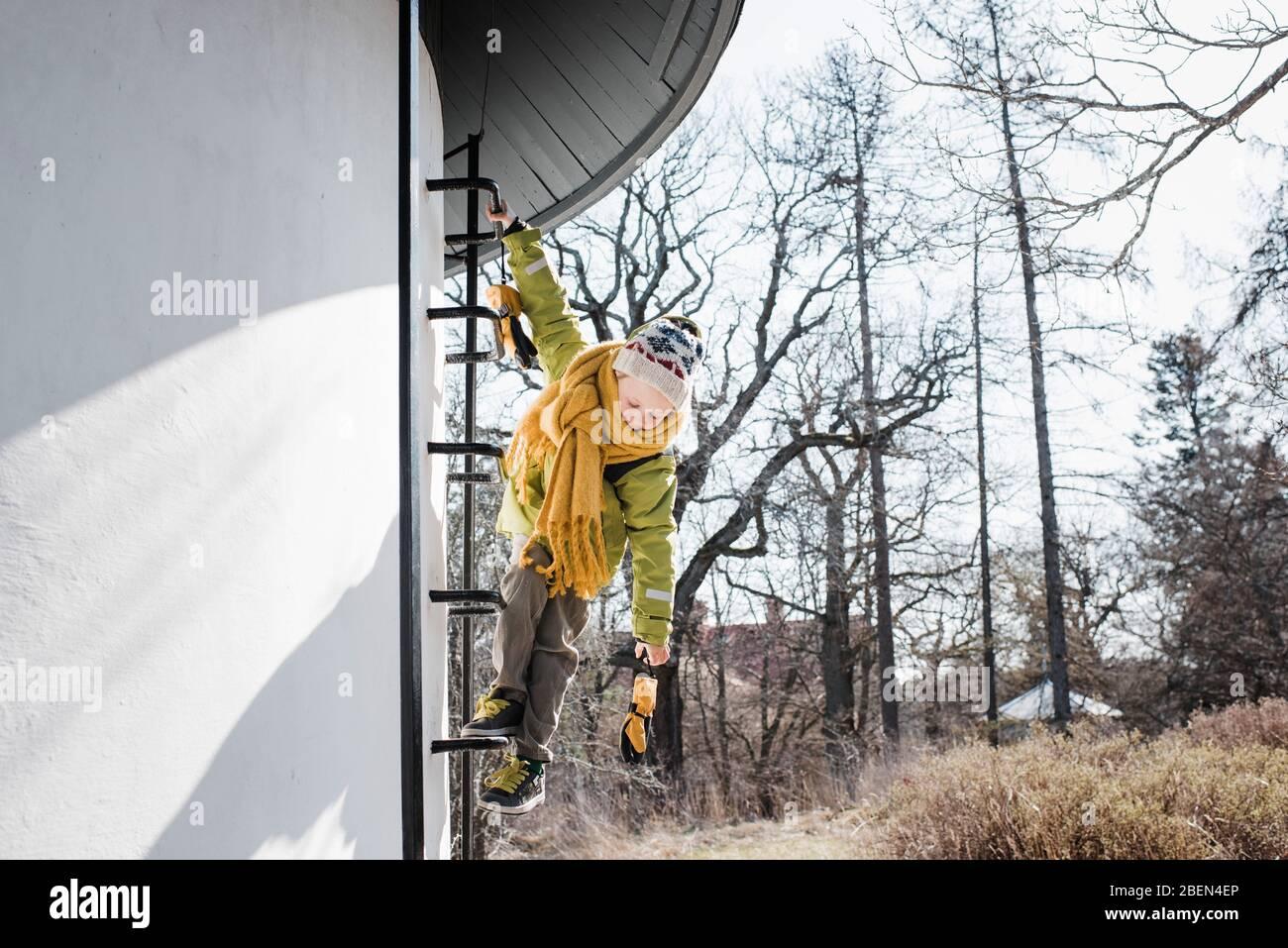 niño trepando una torre de agua en invierno Foto de stock