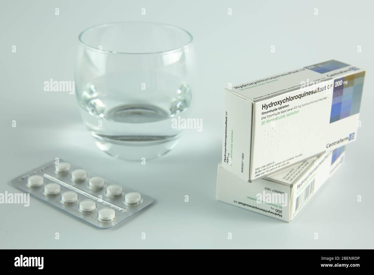 AMSTERDAM, PAÍSES BAJOS - 08 DE ABRIL de 2020: Una caja y tabletas de hidroxicloroquina, también conocida como Plaquenil, con fondo blanco Foto de stock