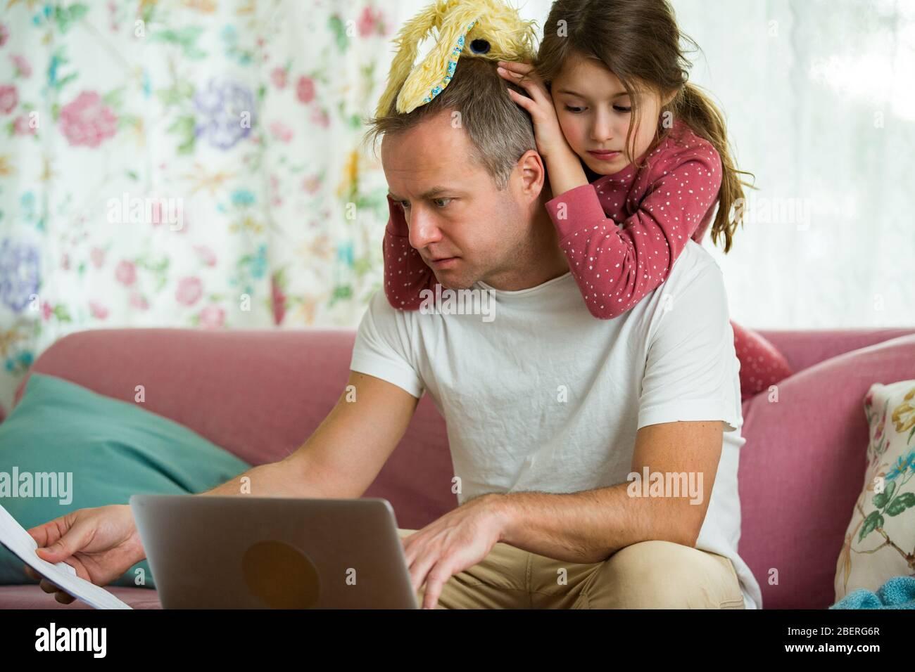 Niño jugando y perturbando a padre trabajando a distancia de casa. Hombre sentado en el sofá con ordenador portátil. Familia pasando tiempo juntos en el interior. Foto de stock