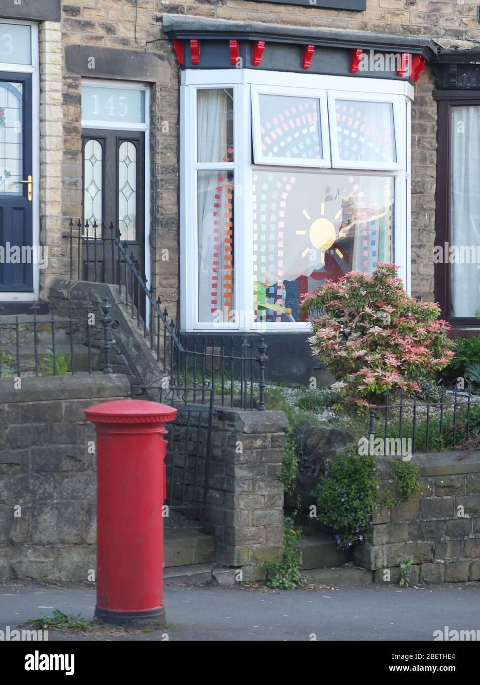 Muestra de papel cortado de color que forma el símbolo de un arco iris y sol como mensaje de esperanza durante la crisis del Coronavirus en la ventana de la bahía de la casa del Reino Unido Foto de stock