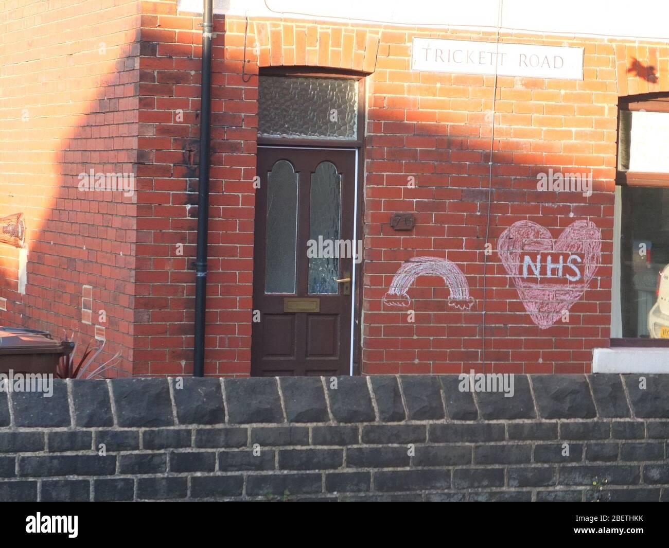 Un mensaje de apoyo y gratitud al NHS con un arco iris calcado en la pared de una casa en Trickett Road, Sheffield durante la crisis del Coronavirus Foto de stock