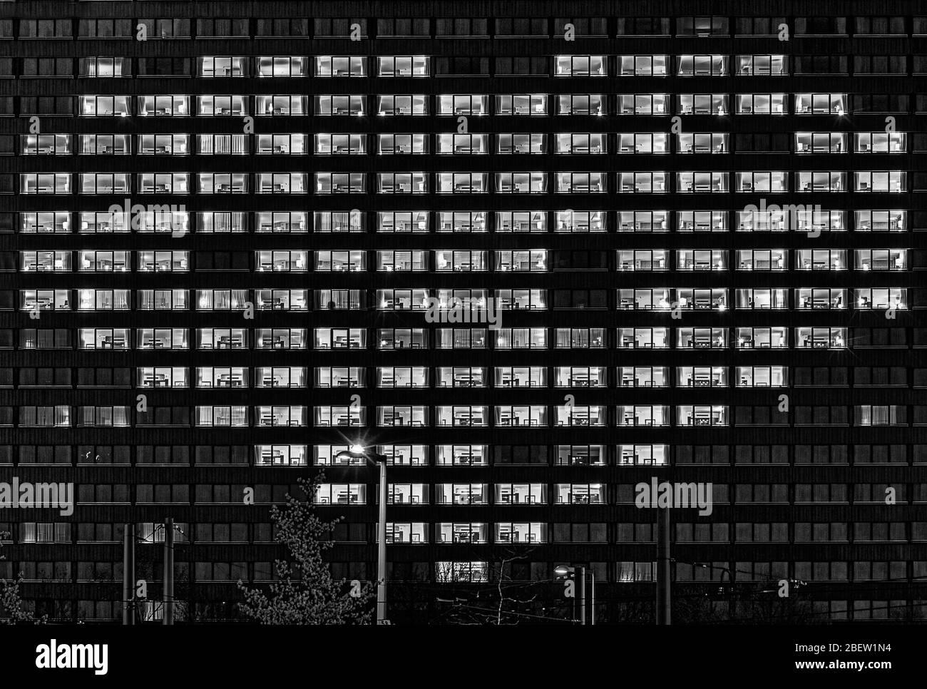 Forma de corazón ventanas iluminadas de un edificio como un gesto para las personas que apoyan a otros como ahora en tiempos duros de la corona virus simbólicamente en negro Foto de stock