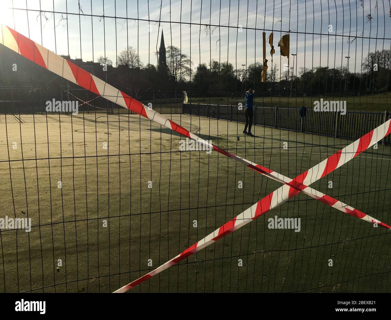 Glasgow, Reino Unido, 16 de abril de 2020. Un hombre hace ejercicios temprano por la mañana en Queen's Park, junto a cercas y cintas que muestran las restricciones en el campo de baloncesto/fútbol, para asegurar el distanciamiento social correcto del público y para prevenir reuniones de personas, durante la actual crisis de salud pandémica del Coronavirus COVID-19. Crédito de la foto: Sir-Hibbert/Alamy Live News. Foto de stock