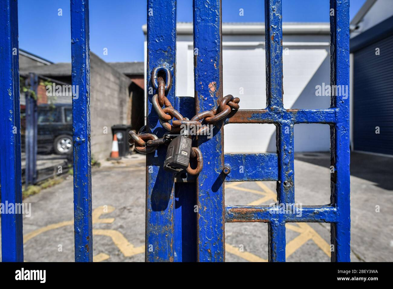 NOTA: IMAGEN 8 DE UN CONJUNTO DE 35 IMÁGENES CON PUERTAS CERRADAS DE NEGOCIOS Y LUGARES QUE ESTÁN CERRADOS DURANTE EL CIERRE del Reino Unido UNA cadena oxidada y candado asegurar puertas de acero pintado de color azul para impedir el acceso a un negocio en una propiedad comercial en Bristol como el Reino Unido sigue en cierre ayudar a frenar la propagación del coronavirus. Foto de stock
