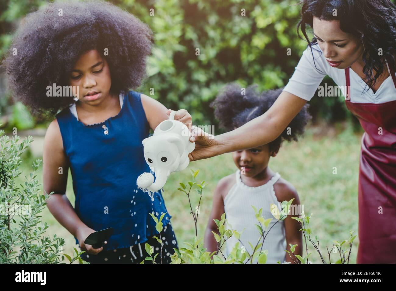 Familia hermosa jardinería riego de plantas verdes actividad con los niños durante la estancia en el hogar para reducir el brote del Coronavirus. Niños regar t Foto de stock