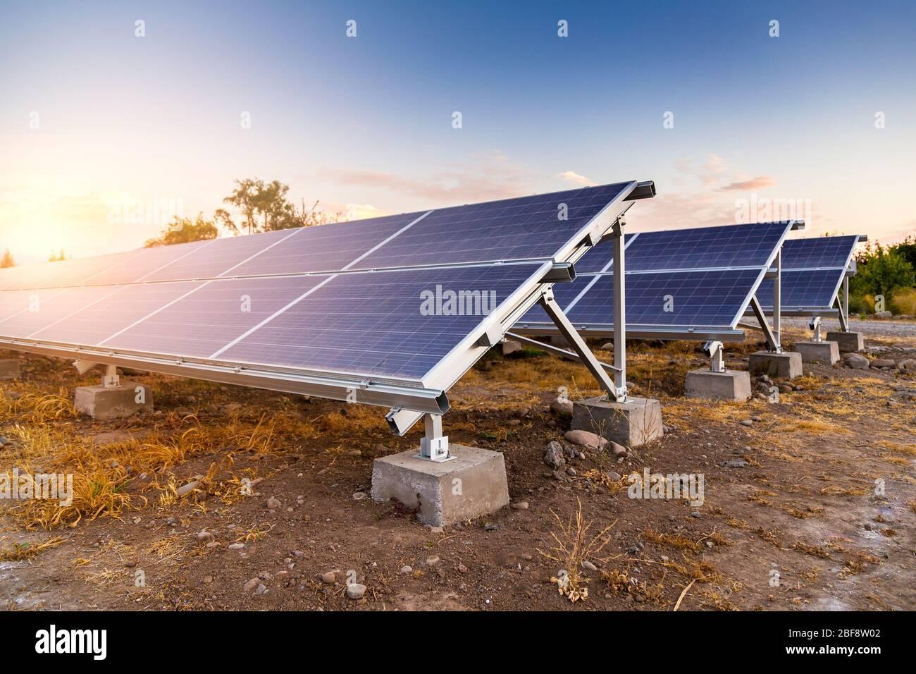 Panel solar sobre el cielo puesta de sol de fondo en el desierto. Generador de energía ecológica. Fuente de energía alternativa. Foto de stock