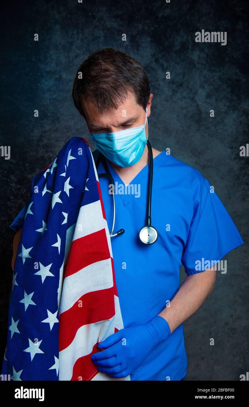 Triste/pensivo, médico masculino en el hospital azul pela con máscara facial y estetoscopio, sosteniendo la bandera americana de Stars & Stripes cerca de su pecho. Foto de stock