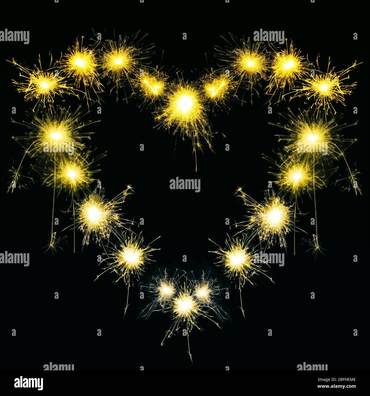Sparklers en forma de corazón sobre fondo negro Foto de stock