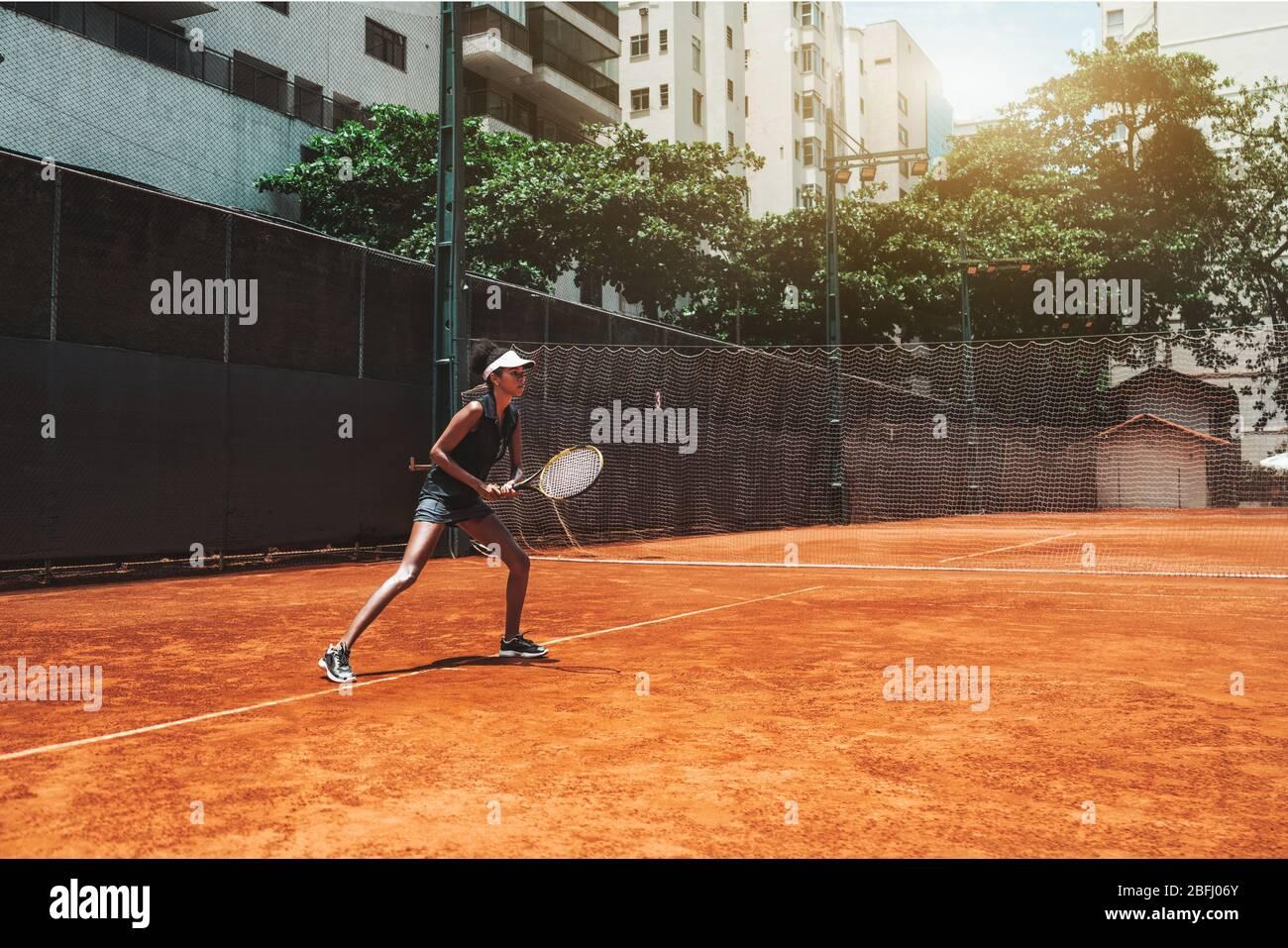 Una joven afroamericana delgada juega al tenis al aire libre en la pista de entrenamiento; hermosa biracial deportes chica en la posición deportiva listo para desviar diez Foto de stock