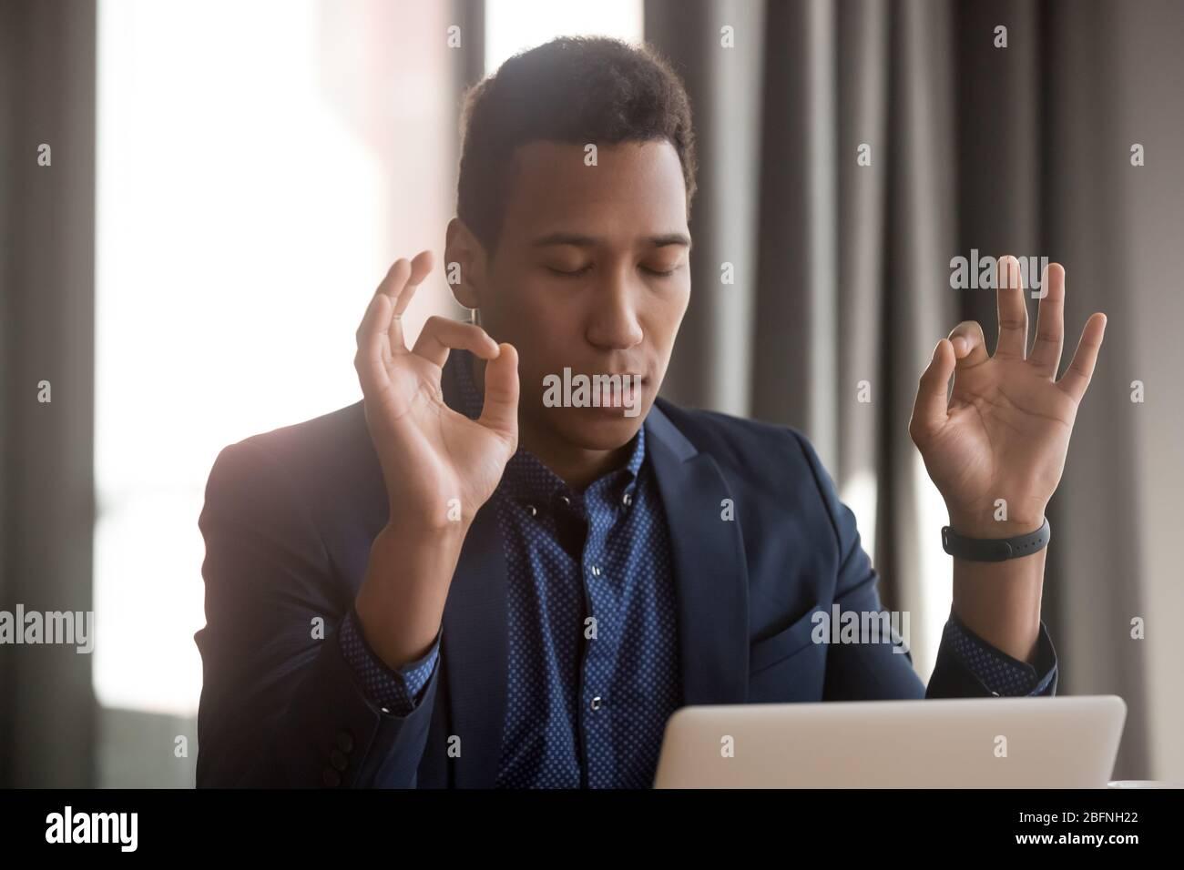 Un hombre de negocios africano cerrado los ojos los dedos doblados reducen las situaciones estresantes Foto de stock