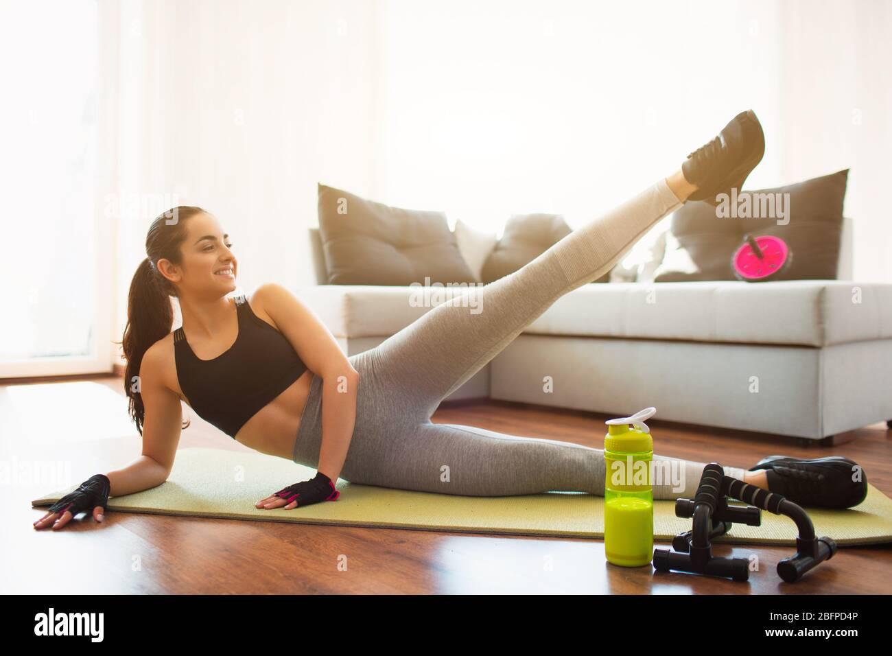 Mujer joven haciendo ejercicio deportivo en la habitación durante la cuarentena. Niña acostada en el lado de la cadera y sujeta la pierna izquierda hacia arriba. Estiramiento de la parte baja del cuerpo. Hacer ejercicio solo Foto de stock
