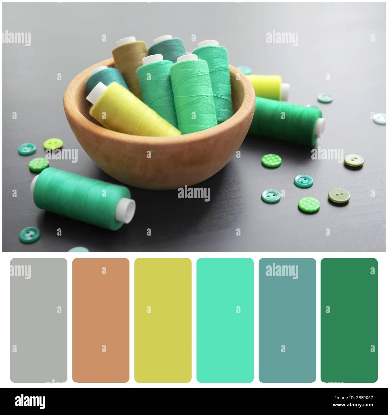 Paleta de colores y cuenco con hilos verdes y botones sobre fondo de madera Foto de stock
