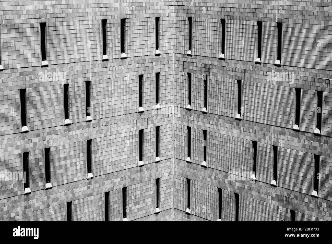 Exterior de ladrillo duro en la cárcel o en la prisión. Las ventanas delgadas permiten entrar un mínimo de luz y ofrecen la máxima seguridad. Foto de stock