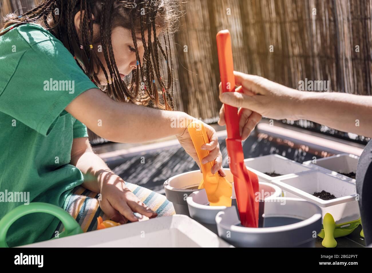 niña y su madre poniendo tierra en las macetas de flores con una pala en el balcón, aficiones en casa, sostenible y concepto de estilo de vida ecológico Foto de stock