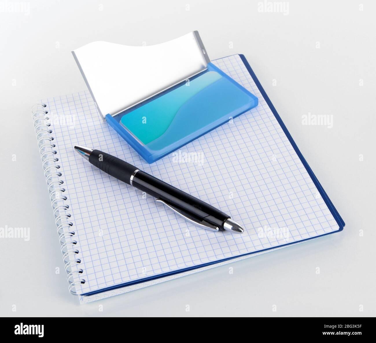 Soporte azul para tarjetas de visita, portátil y bolígrafo aislados en blanco Foto de stock