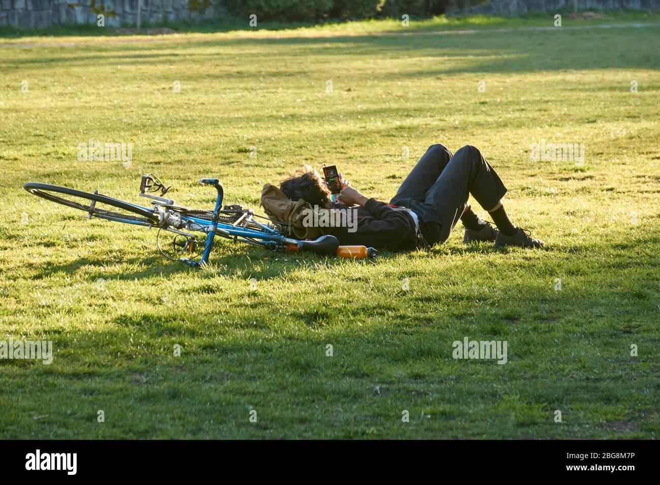 Vancouver, Canadá, 18 de abril de 2020. Un joven se encuentra solo en la hierba utilizando su dispositivo electrónico para permanecer conectado durante la pandemia del COVD-19. Foto de stock
