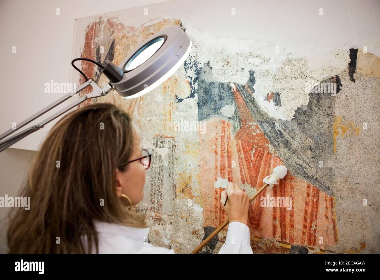 Paz MarquŽs, conservadora-restauradora de lÕËrea, especializada en pintura mural, treballant en un fragmento de pintura mural romˆnica arrenada i trasp Foto de stock