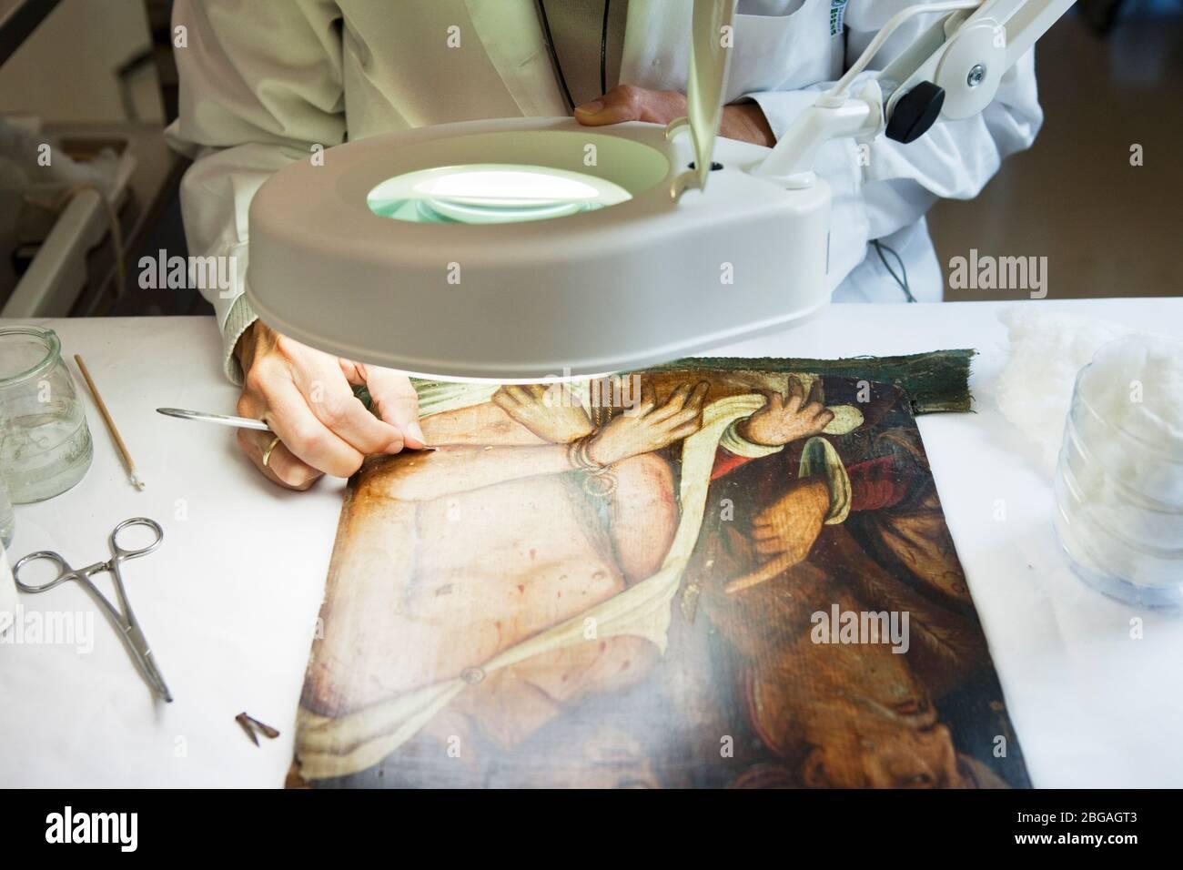 Ëngels Comella, conservadora-restauradora de lÕËrea, especializada en pintura sobre taula, treballant en una obra provinent de la Colegiata de Osuna qu Foto de stock