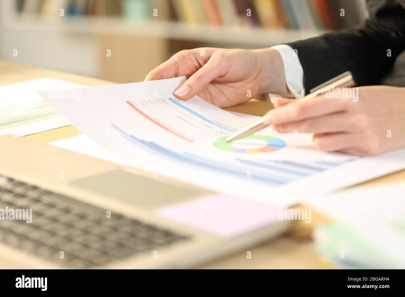 Primer plano de la mujer emprendedora manos ckecking informe de crecimiento gráfico en un escritorio en la oficina doméstica Foto de stock
