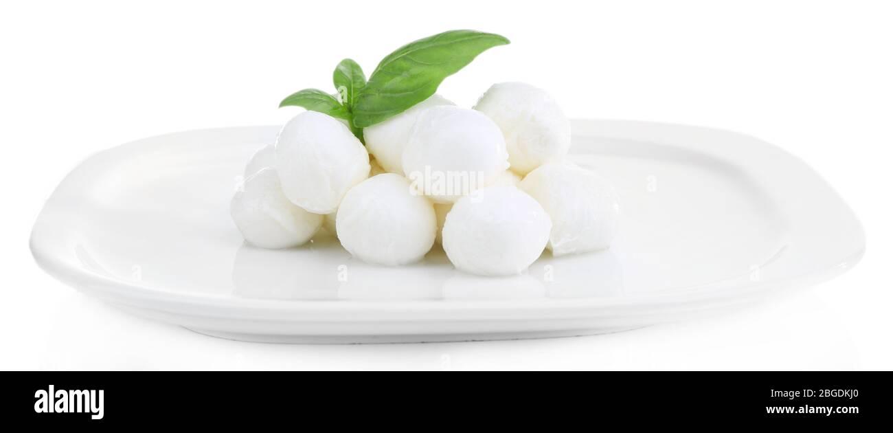 Sabroso queso mozzarella con albahaca en plato aislado sobre blanco Foto de stock