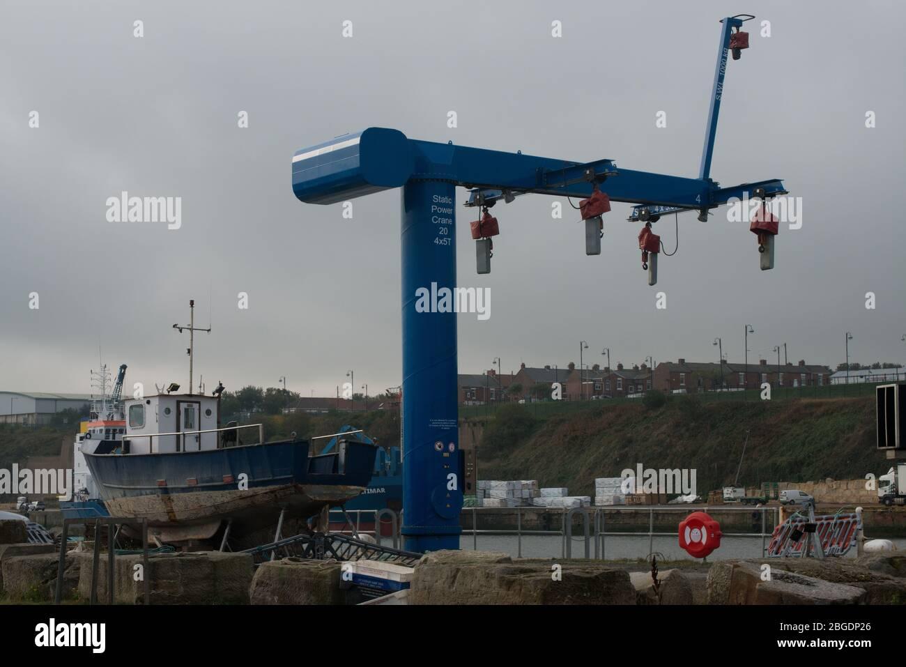 Grúa eléctrica estática en el puerto de Seaham con un pequeño barco levantado en el muelle y la vivienda en terrazas de la ciudad en el fondo Foto de stock