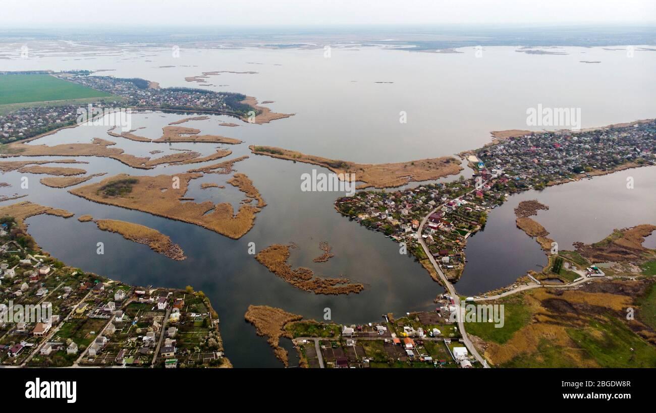 Vista de pájaro del pueblo, calles, carreteras, islas y delta del río en el horizonte. Disparo con drones. Foto de stock
