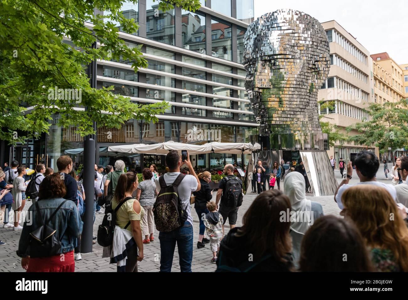 Gente, turista mirando el jefe de Franz Kafka conocido como la estatua de Kafka escultura al aire libre por David Cerny, instalado fuera de las tiendas de Quadrio Foto de stock