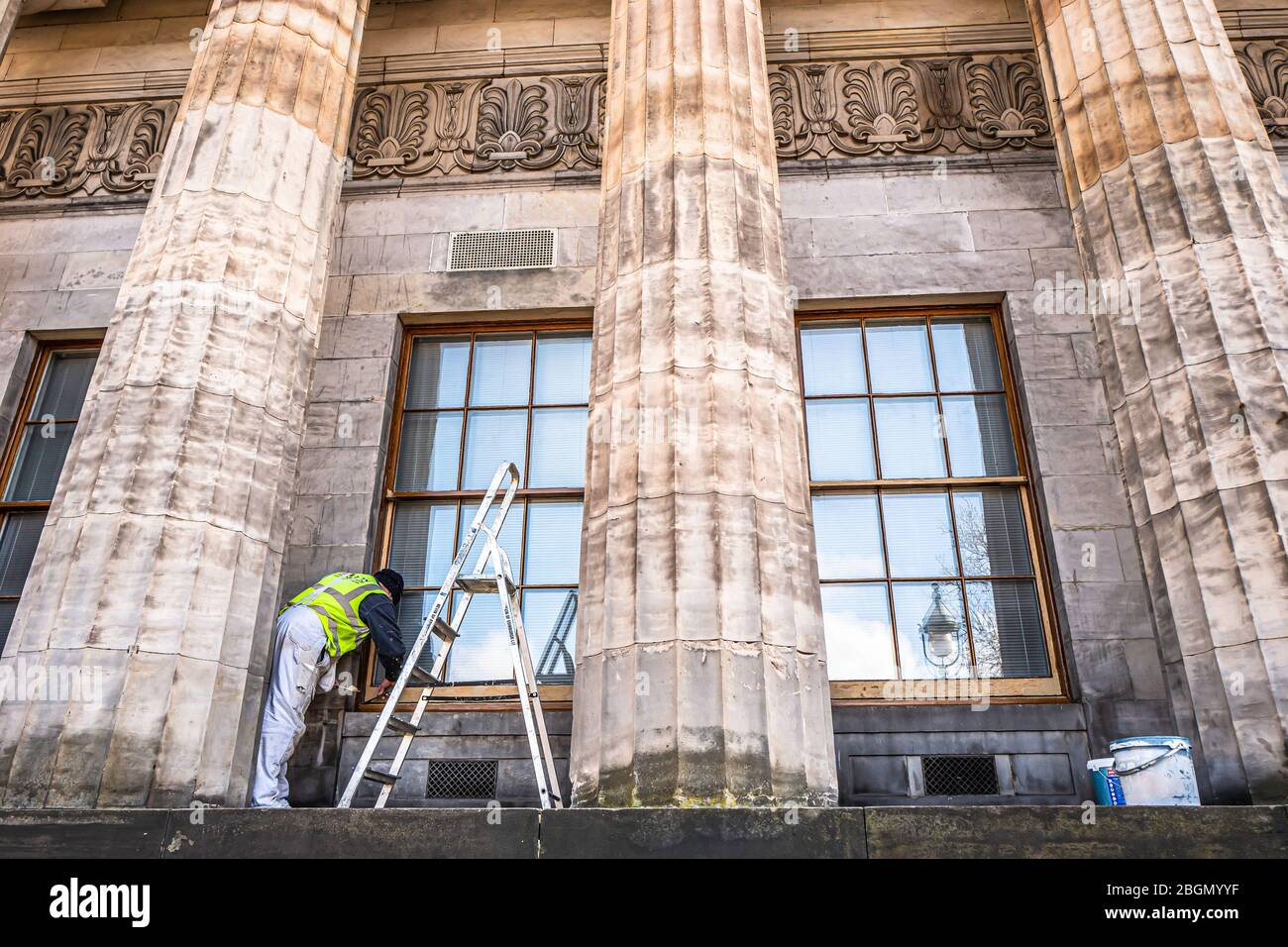 Edimburgo, Lothian, Escocia, Reino Unido. 13 de marzo de 2020. Un pintor y decorador retoca las ventanas de guillotina del edificio neoclásico de la Nación Escocesa Foto de stock