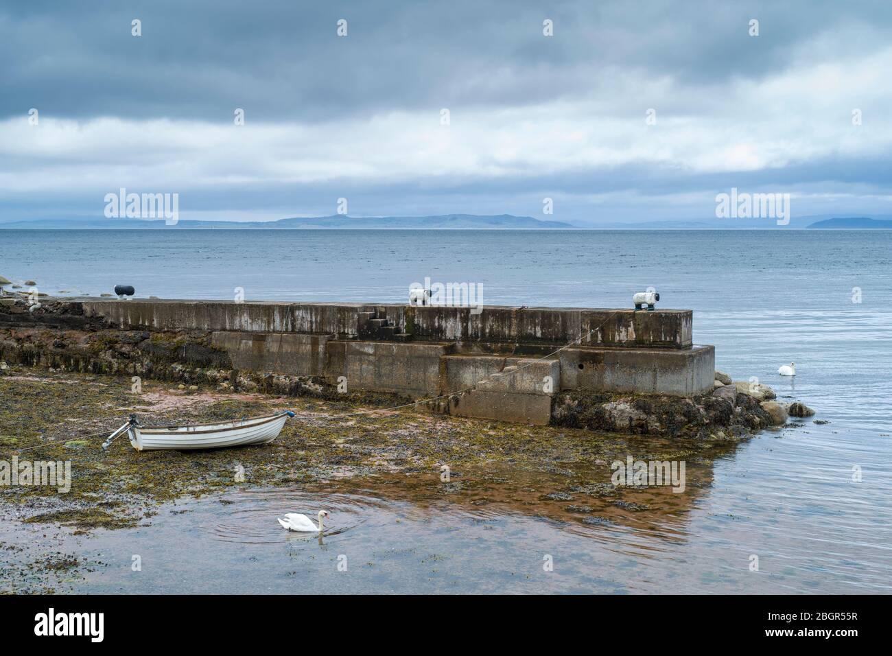 Barco de remo atado a un bolardo de ovejas y amarrado en la orilla del mar en el muelle cerca de Corrie en la Isla de Arran, Escocia Foto de stock