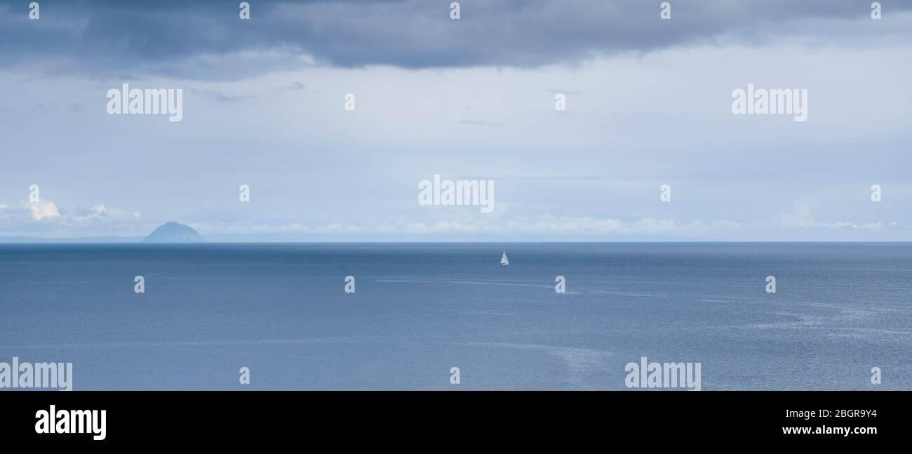 Un yate en el paisaje escocés con en el fondo Ailsa Craig isla en el Firth de Clyde al sur de la isla de Arran, Escocia Foto de stock